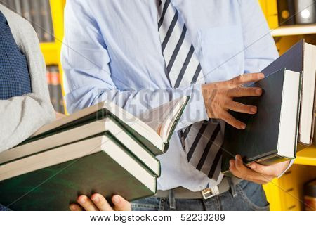 Midsection of male librarian and students holding books in college library