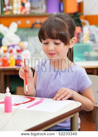 Cute little preschool girl painting at desk in art class