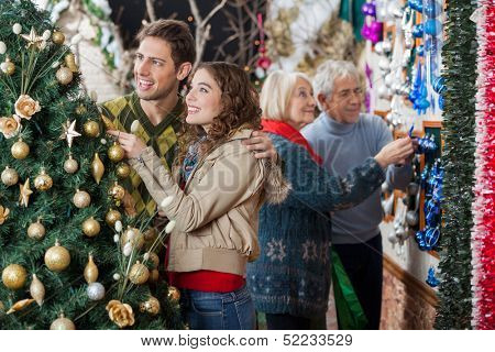 Happy young couple looking at decorated Christmas tree while parents shopping in background at store