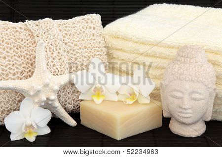 Spa and bathroom accessories with orchids and stone buddha.