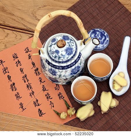 Ginger tea used in chinese herbal medicine with mandarin calligraphy on rice paper and teapot.  Translation describes the medicinal functions to maintain body and spirit health and balance energy.