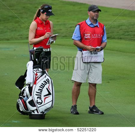 KUALA LUMPUR - OCTOBER 13: Sandra Gal of Germany discusses with her caddy on the next play at the KLGCC course on the final day of the Sime Darby LPGA on October 13, 2013 in Kuala Lumpur, Malaysia.