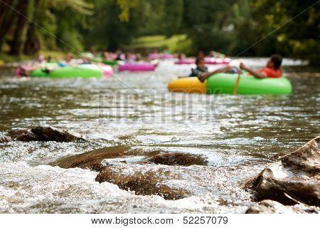 Defocused People Tubing Down Riverapproach Boulders In Focus