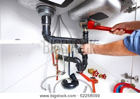 Hands of professional Plumber with a wrench. Clogged sink.