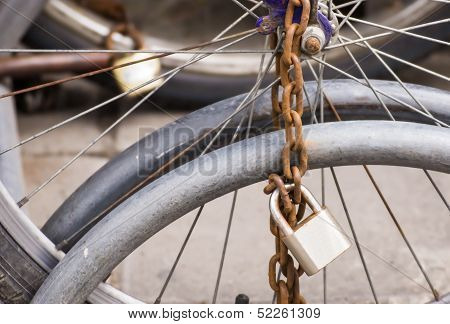 Lock And Chain On A Bicycle ,close Up View Of A Large Lock And Chain Attached To An Old Bicycle Park