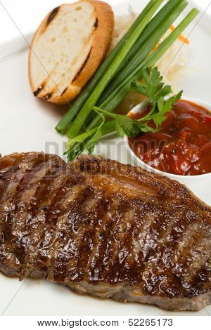 Grilled new york steak with onions and ketchup.