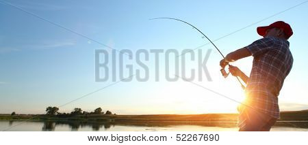 Young man fishing at sunset