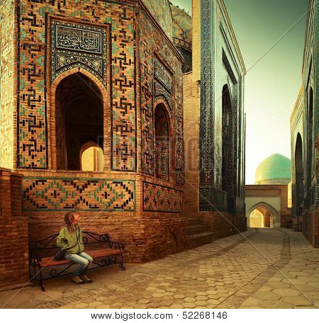 Young lady tourist sitting on a bench and enjoying oriental atmosphere of ancient complex of Shah i Zinda. Samarkand, Uzbekistan