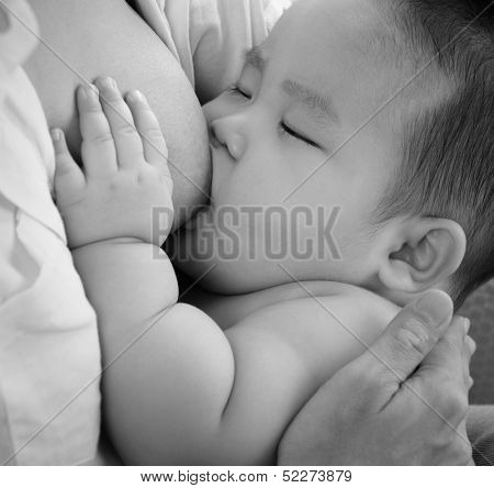 Mother and baby. Close up Asian mother breastfeeding baby boy in black and white tone.