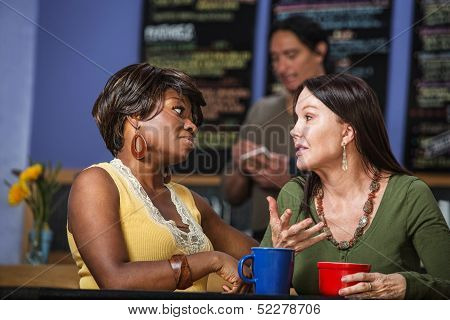 Diverse Friends Talking In Cafe