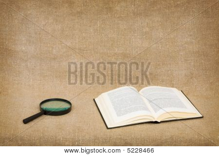 Open Book And Magnifier On Canvas