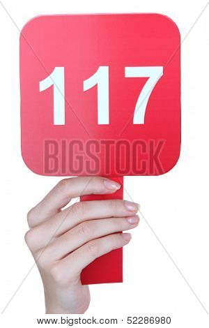 Hand holding  auction paddle isolated on white