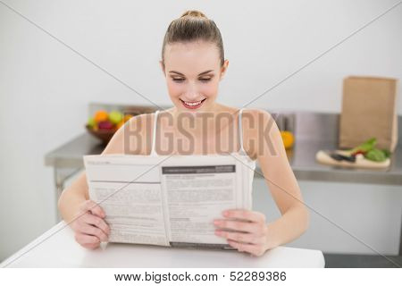 Happy young woman reading a newspaper in the kitchen at home