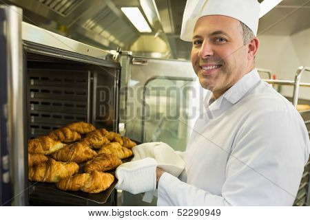 Mature baker smiling proudly at the camera take some croissants out of oven