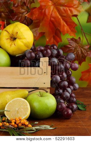 Different fruits with box and branch of sea buckthorn on table on bright background