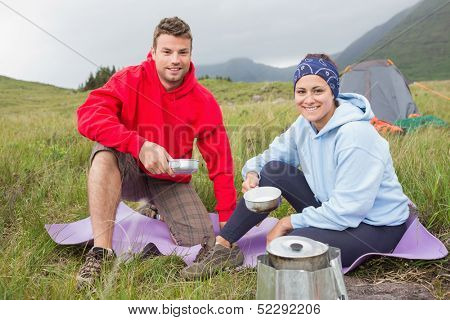 Couple cooking outside on camping trip smiling at camera in the countryside