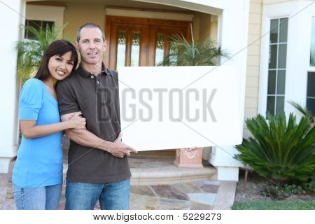 Happy Couple At Home With Sign