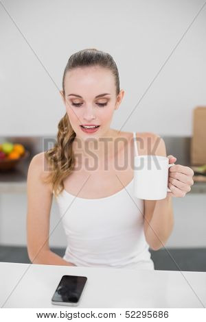 Happy young woman holding a mug looking at smartphone in the kitchen at home