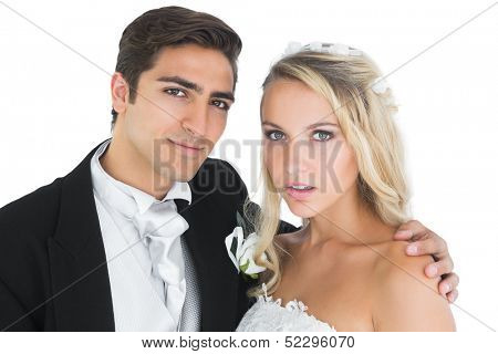 Young bridegroom posing with his wife embracing her on white background
