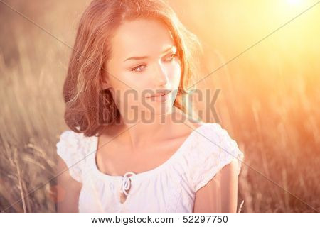 Beauty Romantic Girl Outdoors. Beautiful Teenage Model girl in White Dress on the Field in Sun Light. Blowing Long Hair. Autumn. Glow Sun, Sunshine. Backlit. Warm colors