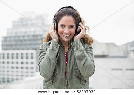 Cheery smiling gorgeous brunette in winter fashion listening to music on urban background