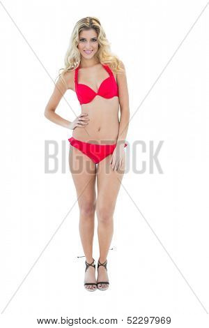 Gleeful blonde model posing with hand on hips wearing red bikini on white background