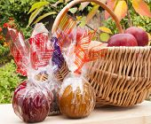 stock photo of toffee  - Caramel chocolate and toffee apples wrapped up in colourful foil next to a basket of freshly picked up red apples - JPG