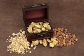 Gold frankincense and myrrh and an old wooden box over brown lokta paper.