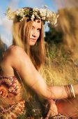 image of hippies  - Attractive hippie girl sitting on a field with floral wreath in her hair - JPG