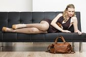 stock photo of leggins  - woman wearing pumps with a handbag lying on sofa - JPG