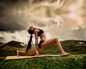 stock photo of surya  - Slim young woman makes warrior yoga pose - JPG