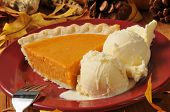 stock photo of pumpkin pie  - A slice of sweet potato or pumpkin pie with vanilla ice cream - JPG