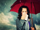 stock photo of rain  - Sneezing Woman with Umbrella over Autumn Rain Background - JPG