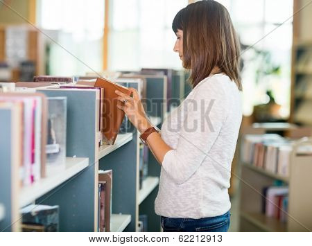 Side view of young college student choosing book in bookstore