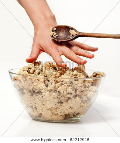 A hand reaching for cookie dough and getting caught
