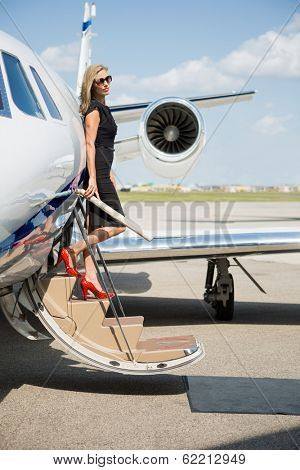 Full length of rich woman disembarking private jet at airport terminal