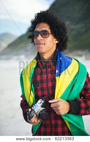 Brasil soccer fan tourist with camera and flag smiling happy at the beach
