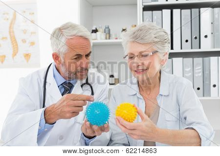 Male doctor showing stress buster balls to senior patient at the medical office