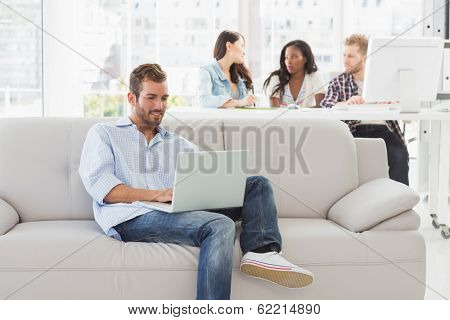 Young designer working on his laptop on the couch in creative office