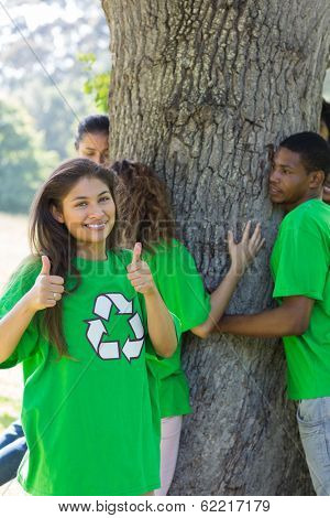 Portrait of female environmentalist gesturing thumbs up with friends hugging tree in background