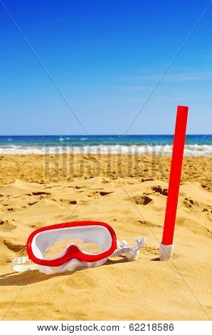 a diving mask and a snorkel in the sand of a beach