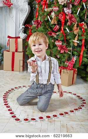 Little boy sits on floor among burning tealights and keeps one on his palm under Christmas tree