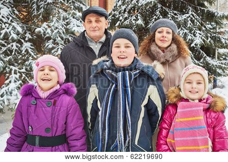 Family of five stands under snow-covered firtrees on winter day