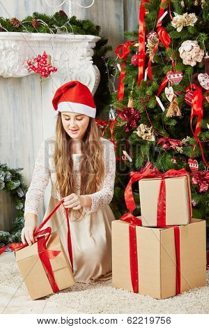 Teenage girl in santa cap sits on furry rug under Christmas tree, untying ribbon  on gift box