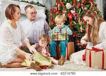Family of five sits under Christmas tree, parents look at their children, wich untie gift boxes