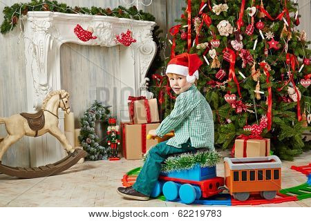 Little boy in Santa cap sits on toy plastic steam engine at room decorated to Christmas celebration