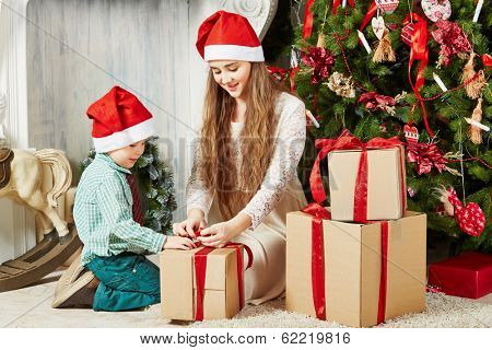 Teenage girl and little boy in santa caps sit on furry rug under Christmas tree untying ribbon  on gift box