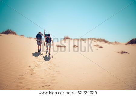 couple hiking uphill  sand dunes