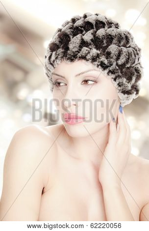 portrait of a beautiful young woman with fur hat isolated on white, work path