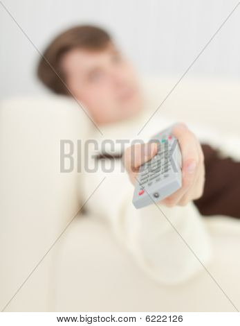 Man Lying On Sofa Uses Remote Control